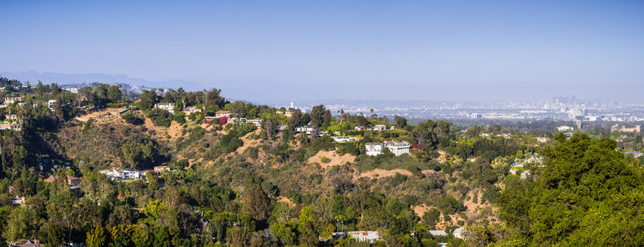 Scattered mansions on one of the hills of Bel Air neighborhood; the downtown skyscrapers visible in the background through a hazy atmosphere; Los Angeles, California