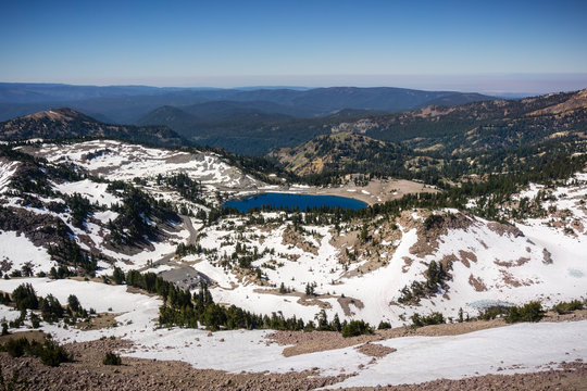 Aerial view of Lake Helen and the surrounding valley as seen from the trail to Lassen Peak; the parking lot for the Lassen Peak trail visible on the left, Lassen Volcanic National Park, California