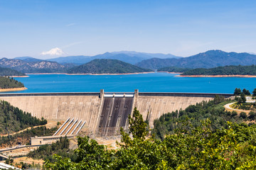 Shasta Dam on a sunny day; the summit of Mt Shasta covered in snow visible in the background; Northern California Wall mural