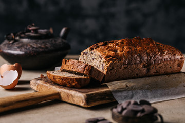Brown handmade loaf of cereal bread served on wooden spade on table cut into slices