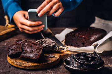 Faceless shot of woman using phone and taking photo of served slices of chocolate bread cake on wooden board