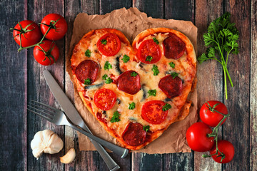 Heart shaped pizza for Valentines Day over a dark wood background. Top view, table scene with ingredients.
