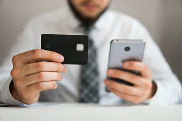 Young businessman with a bank credit card in his hands. Online payments through the phone. Payment of goods online. Smartphone and Internet Commerce. Online trading on the currency exchange.