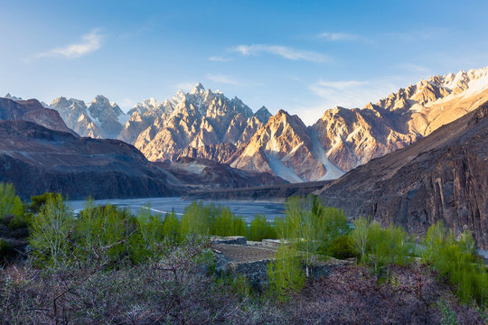 Tupopdan mountain also known as Passu Cones or Passu Cathedral, big rocks all over the place and blue crystal of Hunza river at sunset time ,Northern of Pakistan