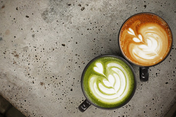 A cup of green tea matcha latte and cup of latte art coffee for background