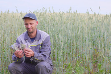 young farmer has a lot of money. The concept of success of business in agriculture.