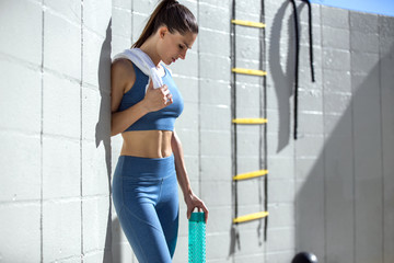 Candid lifestyle portrait of a female athlete at the gym with water bottle and towel