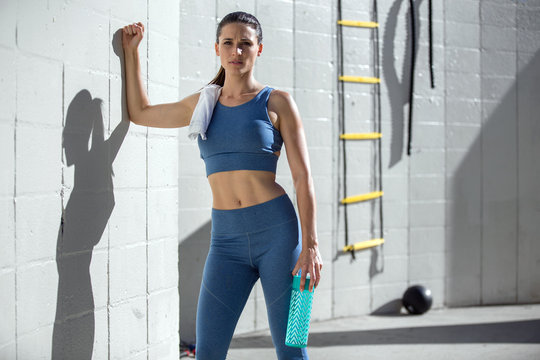 Beautiful brunette model athlete standing against wall with fitness equipment, copy space