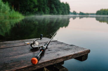 Photo sur Plexiglas Peche Fishing rod, spinning reel on the background pier river bank. Sunrise. Fog against the backdrop of lake. Misty morning. wild nature. The concept of rural getaway. Article about fishing day.