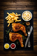 Grilled chicken legs with French fries and vegetables