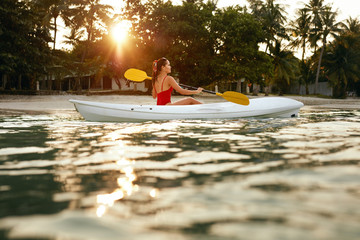 Summer Travel. Woman Kayaking In Sea Water Near Green Island