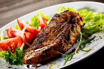 Grilled chicken fillet and vegetables on wooden background