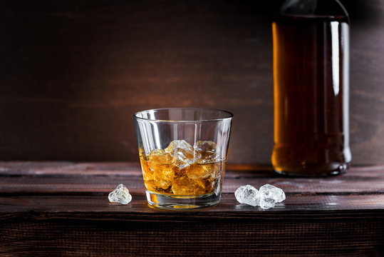 Golden bourbon whiskey with ice on a rustic wooden table in a distillery or bar