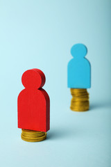 Gender inequality in level of pay concept. Coins on scales and people figures.