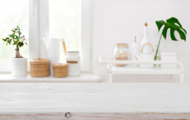 Wooden table on blurred background of kitchen window with utensils