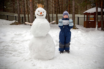A little boy in the winter in the garden stands next to a snowman and looks at the camera smiling