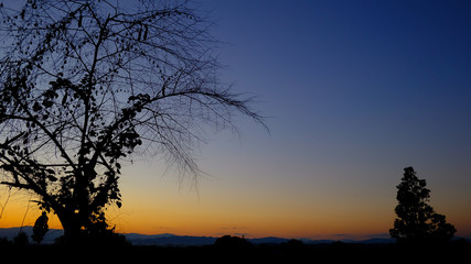 Dark silhouette of mountains with yellow sunset sky, countryside view in the north of Thailand