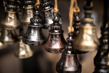 Metallic bells of different colors hanging on strings