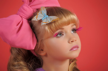 girl blonde with long hair, a big bow and butterflies in her hair