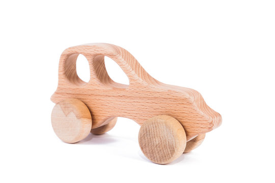 Photo of a wooden car  of beech. Toy made of wood retro car on a white isolated background