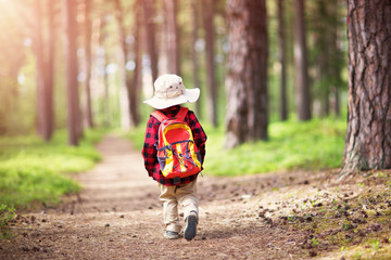 boy going camping with backpack in nature