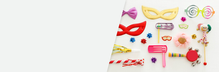 Purim celebration concept (jewish carnival holiday) over wooden white background. Banner.