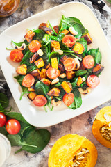 Roasted pumpkin salad with spinach, tomatoes and nuts