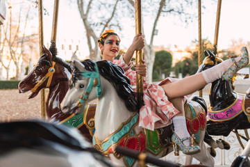 Sensual street performer sitting on horse of merry-go-round