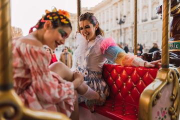 Street artists sitting on merry-go round on fairground