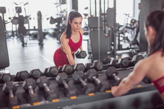 Serious sportswoman working out with dumbbell