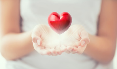 Gentle womens hands and a red heart glowing in his hands. Valentines mothers day and charity concept