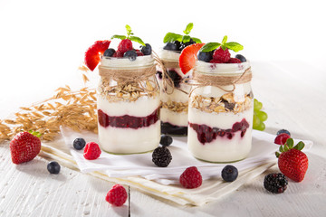 Tasty yoghurts with muesli, fresh berries and jam on wooden table.
