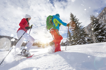 Foto op Plexiglas Wintersporten Snowshoe walkers running in powder snow with beautiful sunrise light.