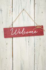 Red sign in front of a white wooden wall - Welcome