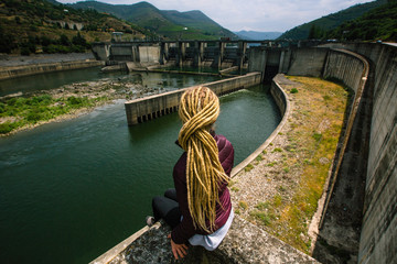 Woman sitting near an abandoned hydroelectric plant.