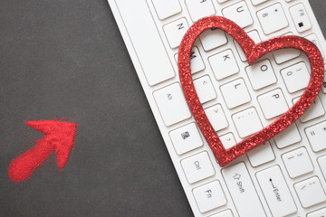 red arrow indicates the red heart on the white keyboard. black background, top view