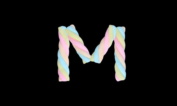 """Marshmallows alphabet """" M """" isolated on black background."""