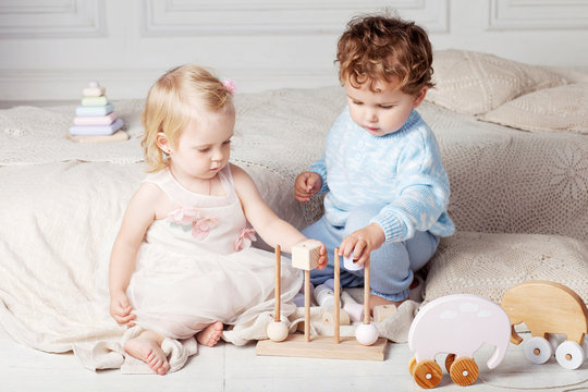 Small children playing together with a wooden toy sorter.  Little boy and girl with natural toys.