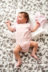 A cute baby girl lying and sleeping on a grey patterned blanket with a dummy in her mouth.