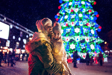 Adult couple hanging out in the city during Christmas time over lights city background and snow at night Fotomurales