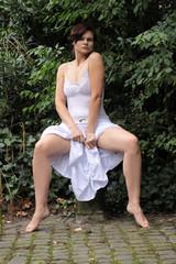 Frau sitzt breitbeinig und hebt Rock hoch