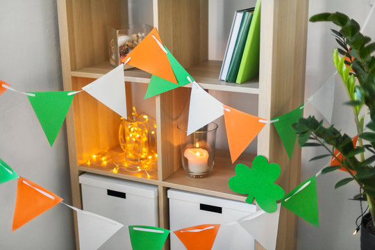 st patricks day, holidays and interior concept - close up of bookcase decorated by festive garland and shamrock for home party
