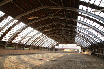 View in an empty indoor riding hall center for horses and riders. The riding school is suitable for dressage and jumping  horses