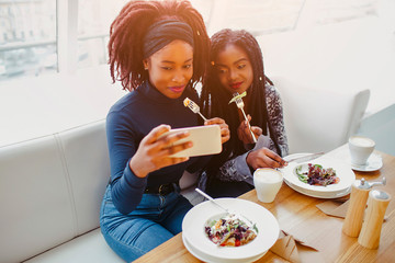 Two african models sit and pose on phone camera. They hold forks with food close to mouth. People are in cafe.