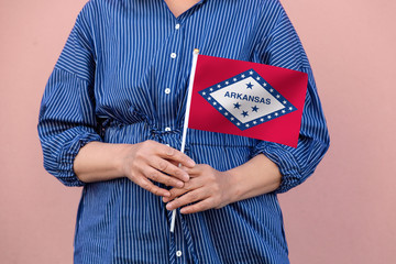 Arkansas state flag. Close up of a woman's hands holding Arkansas flag.