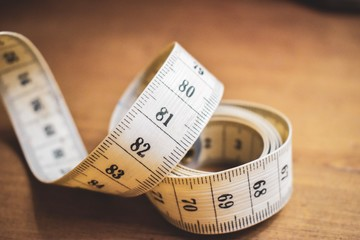 Close-up of white tailor measuring tape on a wood table. Size, metric, fashion, tailoring, fitness and diet concept.