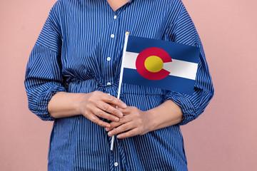 Colorado state flag. Close up of a woman's hands holding Colorado flag.