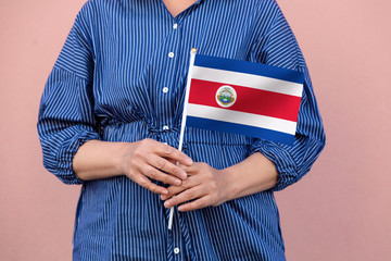 Costa Rica flag. Close up of a woman's hands holding Costa Rican flag.