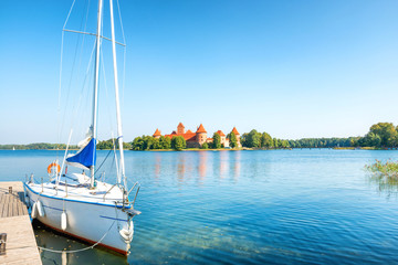 Trakai castle on island lake with white yacht in Lithuania