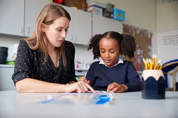 Young female primary school teacher working one on one with a schoolgirl at a table in a classroom,...